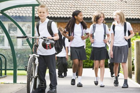 tween boy: Students leaving school one with a bicycle Stock Photo