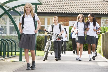 knap sack: Students leaving school one with a bicycle Stock Photo