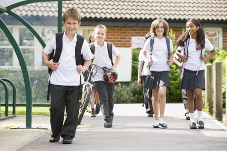ruck sack: Students leaving school one with a bicycle Stock Photo