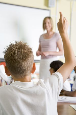 responds: Student volunteering in class with teacher at board (selective focus)