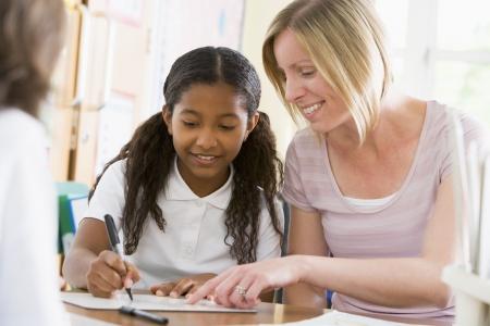 taking note: Studente in classe prendere appunti con insegnante aiutando