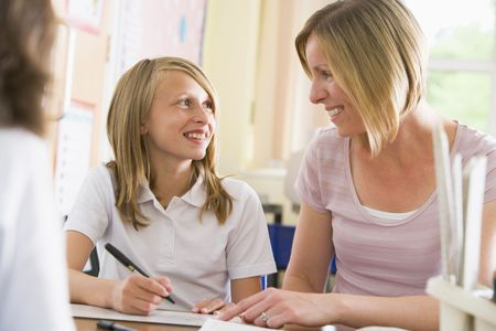 tweens: Student in class taking notes with teacher helping