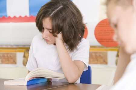 tweeny: Students in class reading book (selective focus)