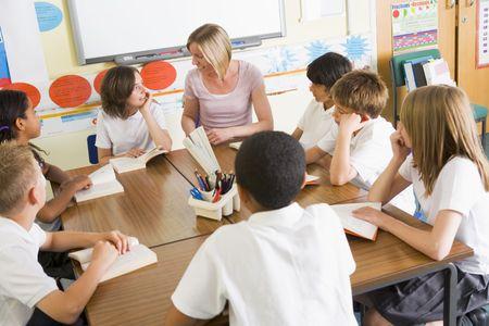 ni�os en la escuela: Los estudiantes en clase la lectura de libros con el maestro  Foto de archivo