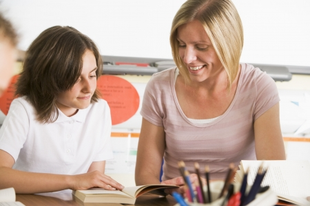 30s adult: Student in class reading book with teacher