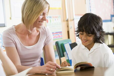mentors: Student in class reading book with teacher