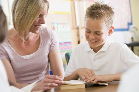 Student in class reading book with teacher photo