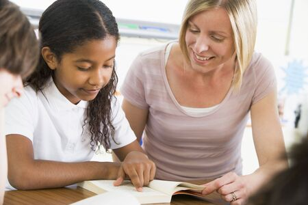 tutoring: Student in class reading book with teacher