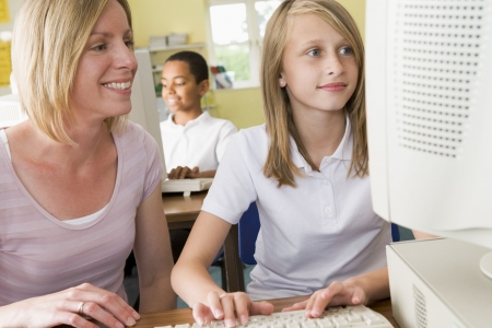 Student and teacher at computer terminal typing with student in background (selective focus) photo