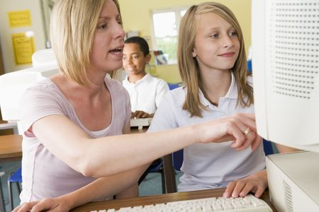Student and teacher at computer terminal with student in background (selective focus) photo