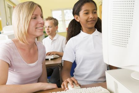 Student and teacher at computer terminal with student in background photo