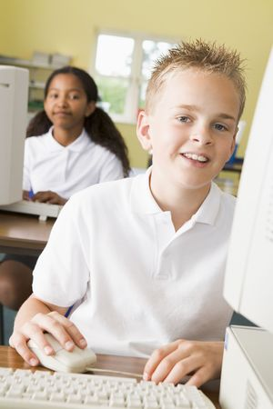 Student at computer terminal with student in background (selective focus) Stock Photo - 3225367