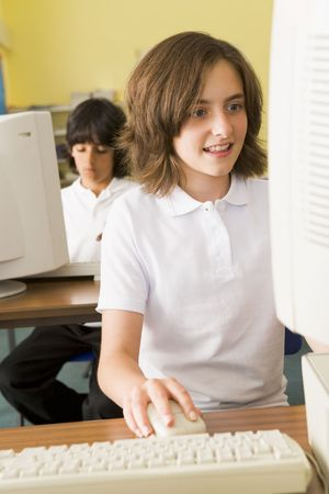 tween girl: Student at computer terminal with student in background (selective focus)
