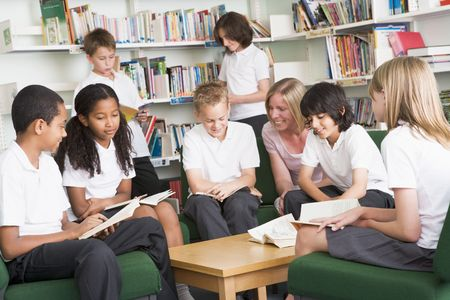Seven students in library reading books with teacher Stock Photo - 3226355