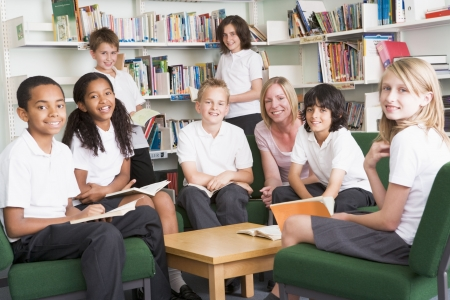 Seven students in library reading books with teacher Stock Photo - 3226349