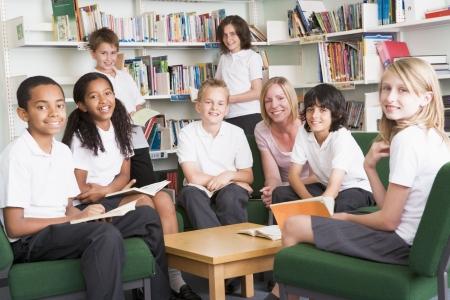 Siete estudiantes en la biblioteca leyendo libros con profesor  Foto de archivo - 3226349