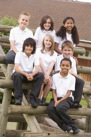 uniform student: Seven students sitting on wooden structure outdoors