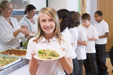 Students in cafeteria line with one holding up her healthy meal and looking at camera (depth of field) photo