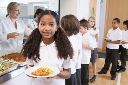 uniform attire: Students in cafeteria line with one holding her healthy meal and looking at camera (depth of field)
