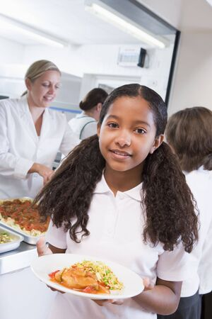 comedor escolar: Los estudiantes en la cafeter�a con una celebraci�n de su comida saludable en busca de c�mara