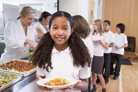 Students in cafeteria line with one holding up her healthy meal looking at camera (depth of field) photo