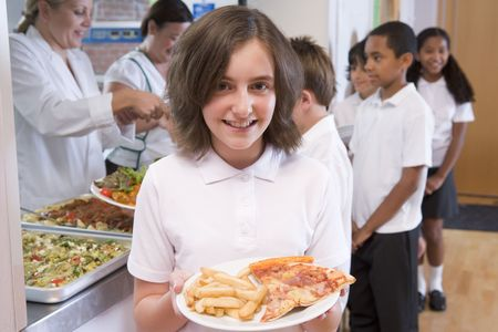 Students in cafeteria line with one holding unhealthy meal looking at camera (depth of field) Stock Photo - 3225440