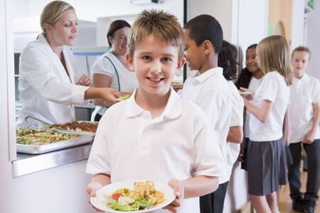 uniform attire: Students in cafeteria line with one holding his healthy meal and looking at camera (depth of field)