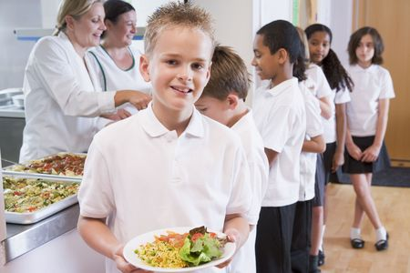 junior education: Students in cafeteria line with one holding his healthy meal and looking at camera (depth of field)