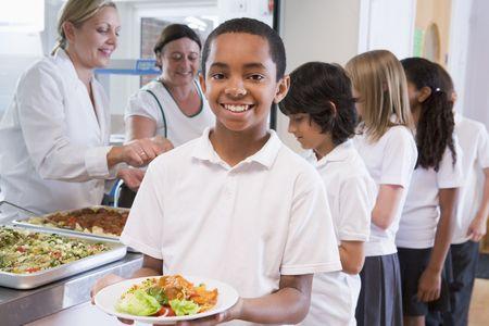 comedor escolar: Los estudiantes en la cafeter�a con una celebraci�n de su comida saludable y mirando a c�mara (profundidad de campo)