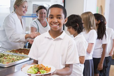 tweens: Students in cafeteria line with one holding his healthy meal and looking at camera (depth of field)