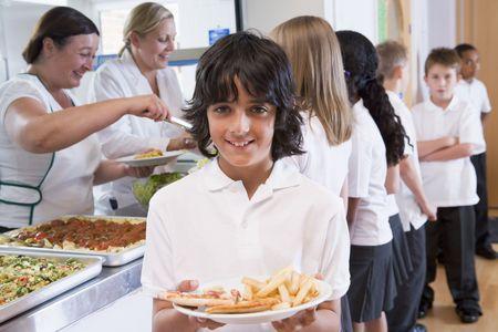 comedor escolar: Los estudiantes en la cafeter�a con una celebraci�n de su comida poco saludable y mirando a c�mara (profundidad de campo)  Foto de archivo