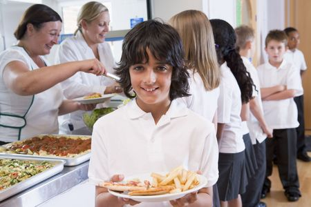 frontal views: Students in cafeteria line with one holding his unhealthy meal and looking at camera (depth of field)