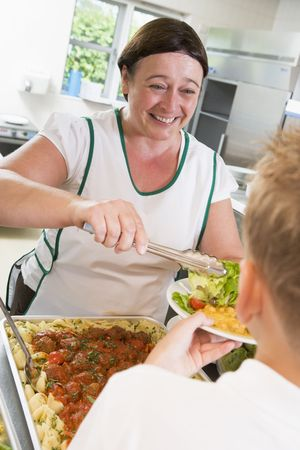 dinner wear: Lunch lady serving salad to student