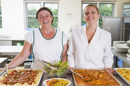 school lunch: Two lunch ladies standing behind full lunch service station