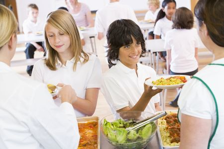 Students in cafeteria line being served by lunch ladies photo