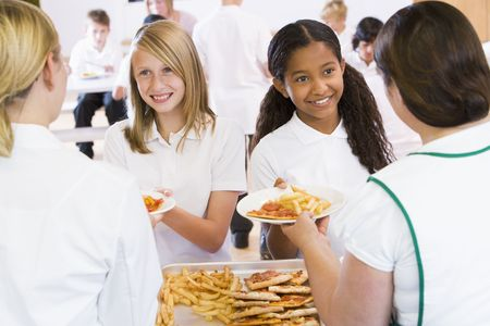 junior education: Students in cafeteria line being served by lunch ladies Stock Photo
