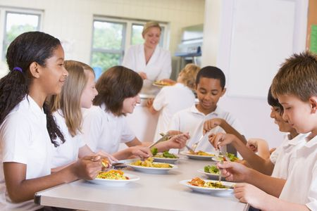 frontal views: Students sitting at cafeteria table eating lunch (depth of field) Stock Photo