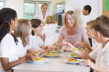 Students sitting at cafeteria table eating lunch with teacher photo