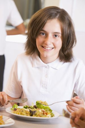 Student in cafeteria eating lunch (selective focus) photo