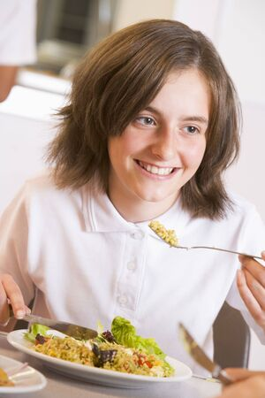 tweeny: Student in cafeteria eating lunch (selective focus) Stock Photo