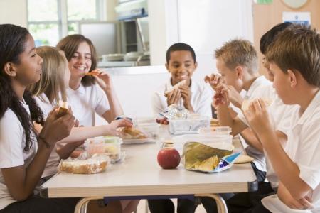 comedor escolar: Los estudiantes sentados en la cafeter�a mesa de comer el almuerzo (profundidad de campo)