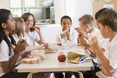 school lunch: Students sitting at cafeteria table eating lunch (depth of field) Stock Photo