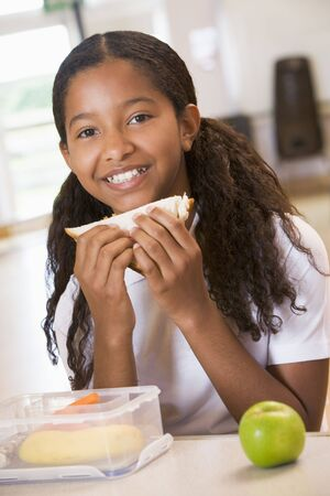 tweens: Student in cafeteria eating lunch (selective focus) Stock Photo