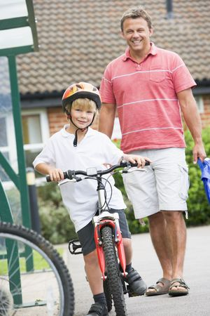 men 45 years: Father and Son outside school with bicycle
