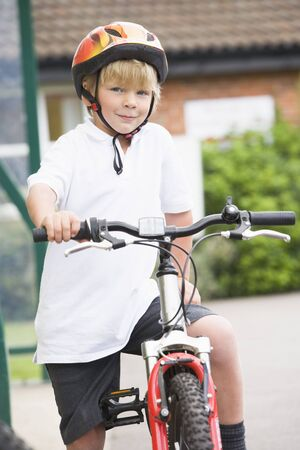 Young boy getting on bicycle outside school photo