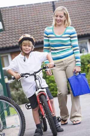 school uniforms: Mother and son outside school with bicycle