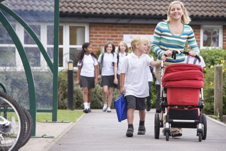 prams: Woman and young boy pushing a stroller outside school with students in background (selective focus) Stock Photo