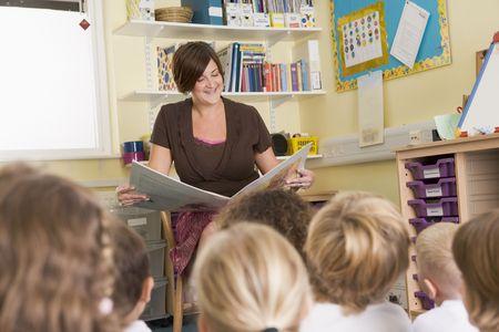 femme professeur: Enseignant en classe de lecture avec des �l�ves de premier plan (s�lective focus)