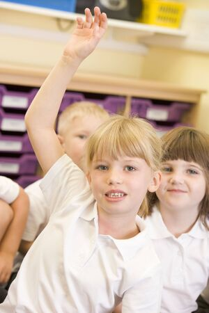 responds: Student in class volunteering with students in background (selective focus) Stock Photo