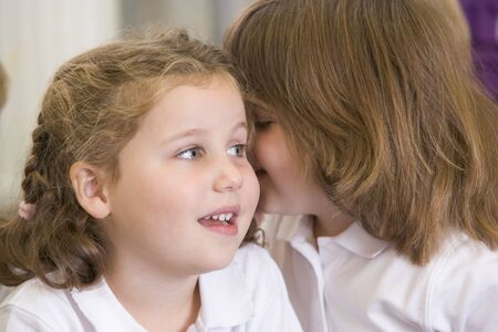 misbehaving: Two students in class whispering (selective focus) Stock Photo